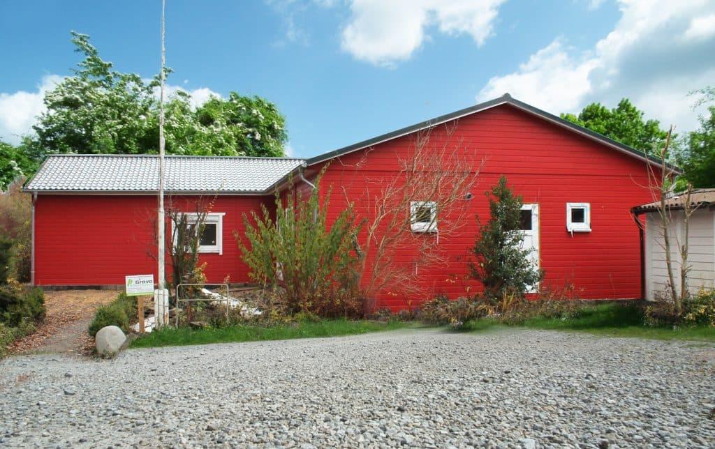 Rotes Holzhaus mit Softlineschalung, weißen Fenstern und Türen