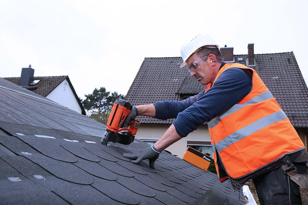 Ein Monteur bei der Eindeckung eines Daches