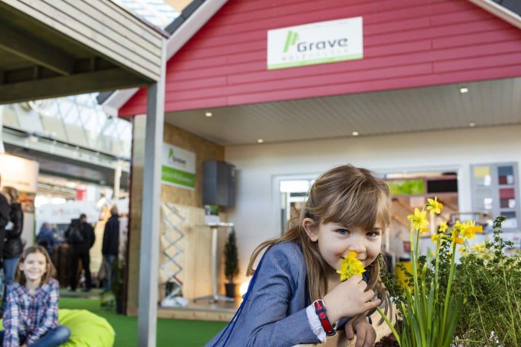Holzhaus auf der B.I.G. Baumesse mit Kindern und Pflanzen im Vordergrund.